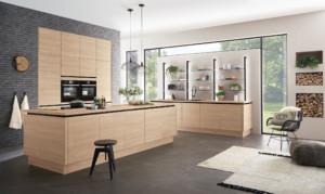 Modernes, griffloses Küchendesign mit sehr natürlich wirkenden Oberflächen in Eiche-Nachbildung. Besondere Eyecatcher sind auch die Kücheninsel sowie die schwarzen Regal-Stollen mit indirekter Beleuchtung. Ihre Lichtfarbe lässt sich individuell steuern. (Foto: AMK)