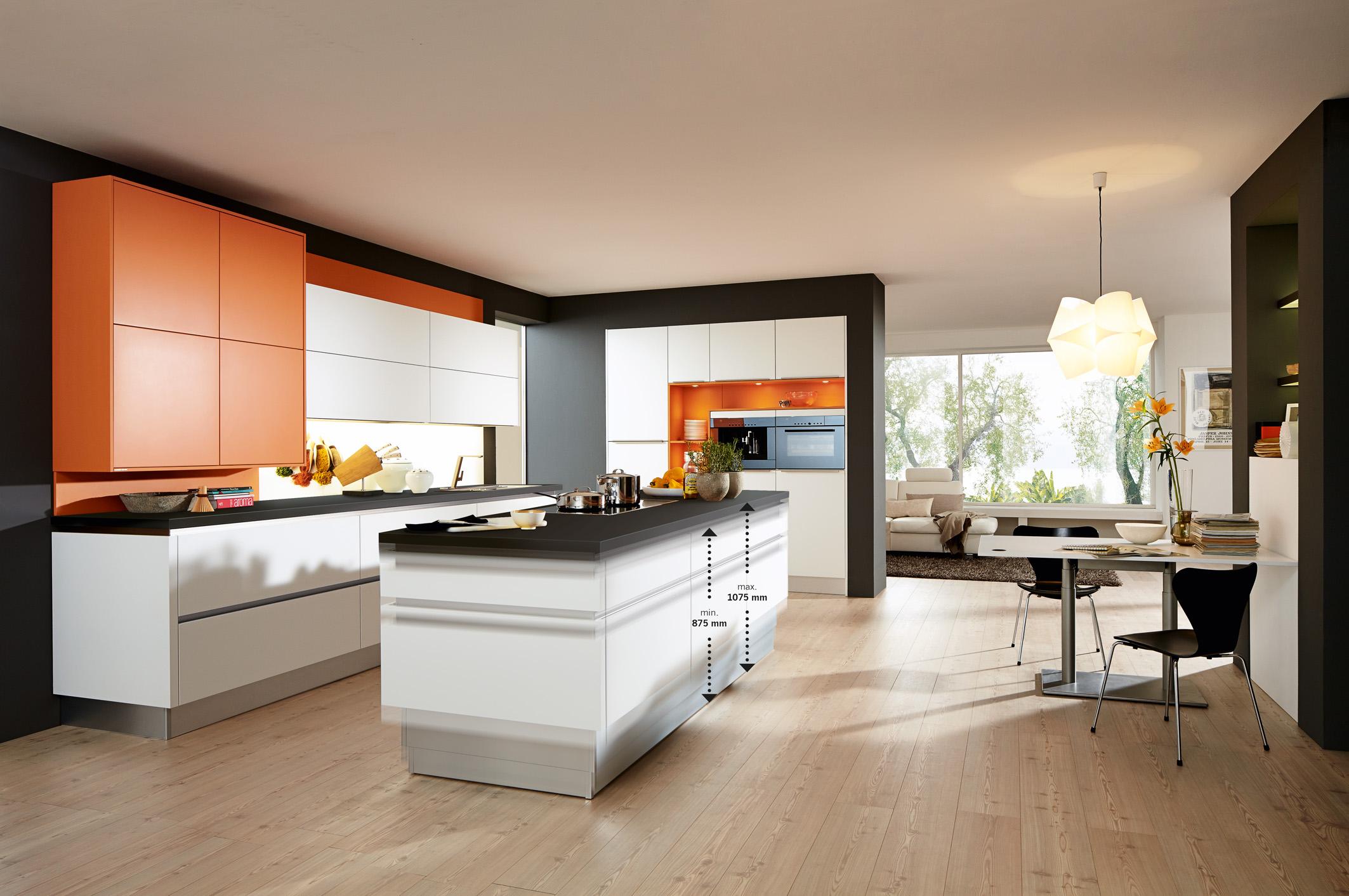 """So angenehm wie möglich wollen es die Menschen beim Vorbereiten von Speisen, beim Kochen und dem anschließenden Aufräumen haben. """"Die deutsche Küchenindustrie verfügt über ein vielfältiges Sortiment für ergonomisches, bequemes und ermüdungsfreies Arbeiten in der Küche"""", sagt Volker Irle, Geschäftsführer der Arbeitsgemeinschaft Die Moderne Küche e.V. (AMK). """"Die intelligenten Lösungen erleichtern den Alltag und erhalten zugleich den Spaß am Kochen."""" Damit die Tätigkeiten in der Küche möglichst bequem erledigt werden können, sind optimale ergonomische Arbeitshöhen besonders wichtig. Falls Paare unterschiedlich groß sind, geraten sie mit angestammten Küchenentwürfen schnell an ihre Grenzen. """"Als Lösung bieten sich höhenverstellbare Kochinseln an"""", berichtet Irle. Mit ihrer Hilfe findet jedes Familienmitglied seine individuelle Arbeitsposition. Dank eines Hubsockelsystems kann die Arbeitshöhe um bis zu 20 Zentimeter verstellt werden. Mit elektromotorischen Antrieben lassen sich die Arbeitsplatte und die Küchenschränke leise und stufenlos anheben und absenken. Egal, ob die Hobbyköche 1,60 Meter oder 2 Meter groß sind – jeder findet eine ideale Arbeitshöhe, um bequem Gemüse oder Fleisch zu schneiden, Gerichte auf dem Kochfeld zuzubereiten und Töpfe im Spülbecken abzuwaschen. Auf diese Weise werden eine ungünstige Körperhaltung und die daraus oftmals resultierenden Rückenbeschwerden vermieden. Mehrere Höhen lassen sich fest einprogrammieren. Zudem müssen sich große Menschen beim Griff in die Unterschränke weniger stark bücken, da auch die Schränke mit in die Höhe gefahren werden. Ganz auf die individuellen Bedürfnisse einrichten lassen sich auch Arbeitstische für die Küche. Mit Hilfe einer um 50 Zentimeter höhenverstellbaren Tischplatte kann daran sowohl bequem gespeist, als auch gearbeitet oder in Stehhöhe mit Freunden geplaudert werden. Als Vorbild dienen Steh-Sitz-Schreibtische, die inzwischen in vielen Büros Einzug gehalten haben und für eine Abwechslung bei der Arbeit"""