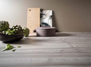 Wie sehr verschieden, schön und ausdrucksstark die Anmutung einer Küchenarbeitsplatte und Nische sein kann, zeigen diese Beispiele in Keramik, fein bedrucktem Glas matt, dunklem Naturstein und Echtholz. (Foto: AMK)