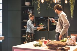 In dieser smarten Lifestyle-Wohnküche werden alle WLAN-fähigen Hausgeräte einfach per App gesteuert – von überall aus: beispielsweise zum Vorheizen der Einbau-Backöfen oder damit sie eine Nachricht schicken, wenn die Speisen fertig sind. Die Backöfen lassen sich auch via Sprachbefehle steuern. (Foto: AMK)