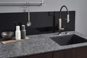Der Wandbereich an der Spüle lässt sich – wie hier mit Stangen – zur Aufbewahrung von Küchenutensilien nutzen. (Foto: AMK)